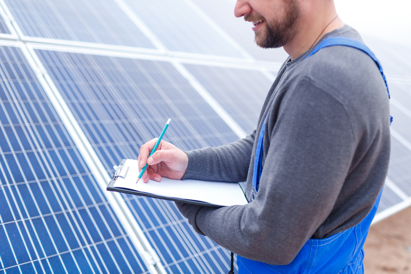A young worker with a smile in blue uniform with a tablet makes notes close-up against a background of solar panels